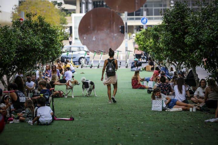 תל אביב, צעירים יושבים על הדשא, אנשים יושבים על הדשא